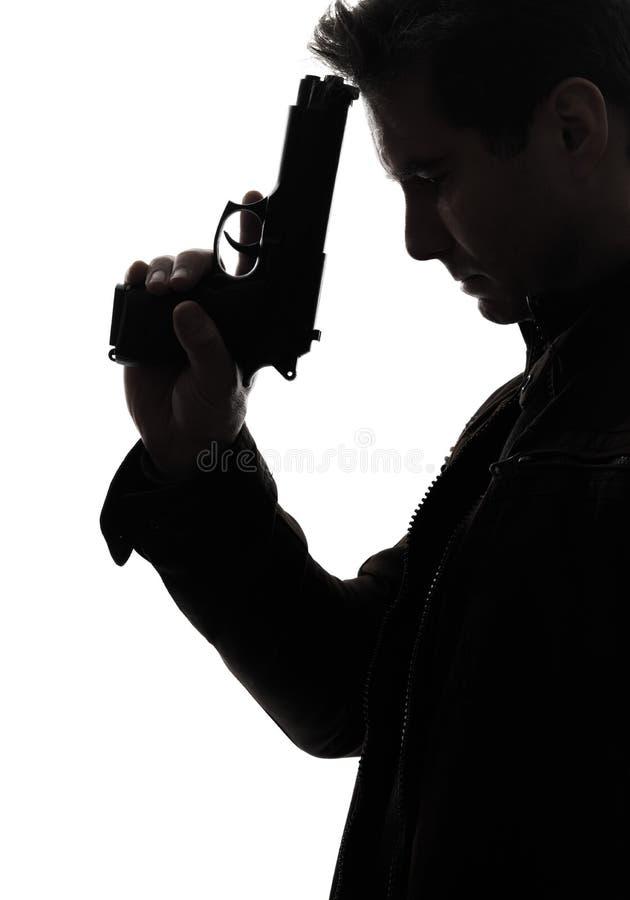 Siluetta del ritratto della pistola della tenuta del poliziotto dell'uccisore dell'uomo fotografia stock
