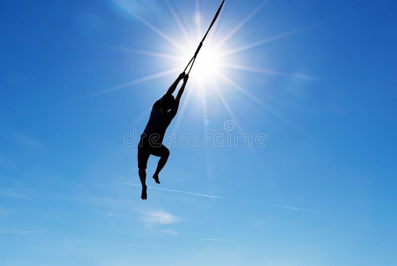 Siluetta del saltatore sopra il fondo del cielo blu fotografia stock libera da diritti
