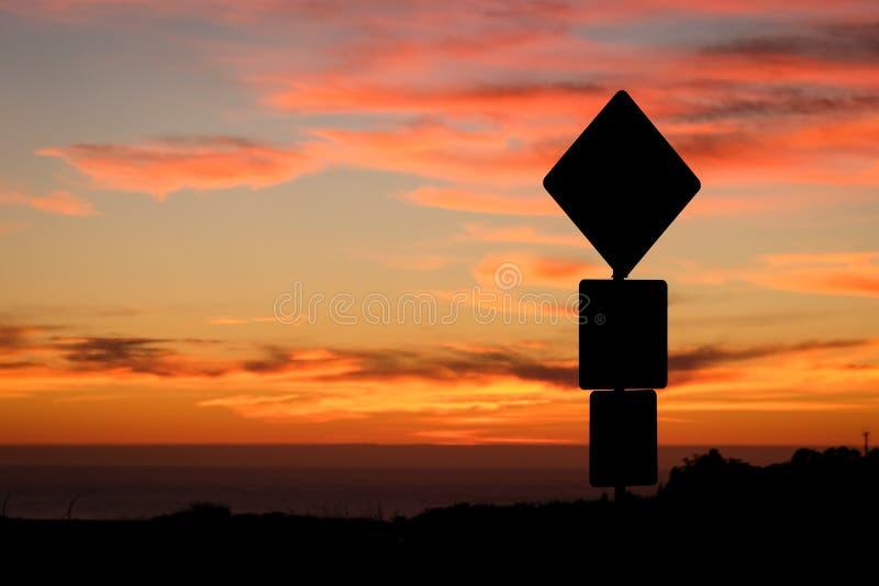 Siluetta del segnale stradale e tramonto variopinto fotografia stock