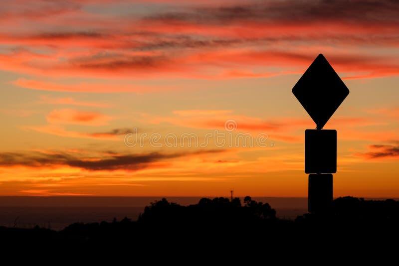 Siluetta del segnale stradale e tramonto variopinto immagini stock