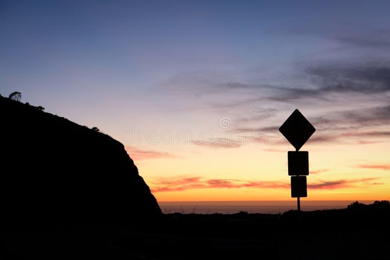 Siluetta del segnale stradale e tramonto variopinto immagine stock