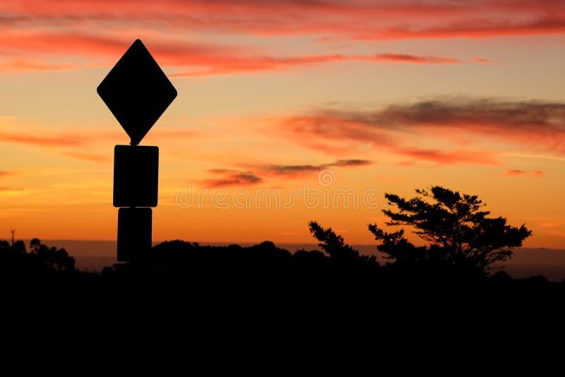 Siluetta del segnale stradale e tramonto variopinto immagine stock libera da diritti