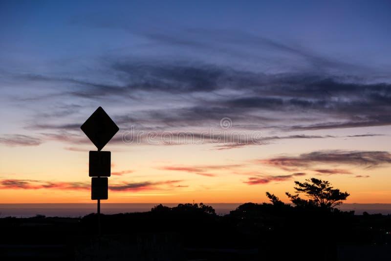 Siluetta del segnale stradale e tramonto variopinto fotografia stock libera da diritti