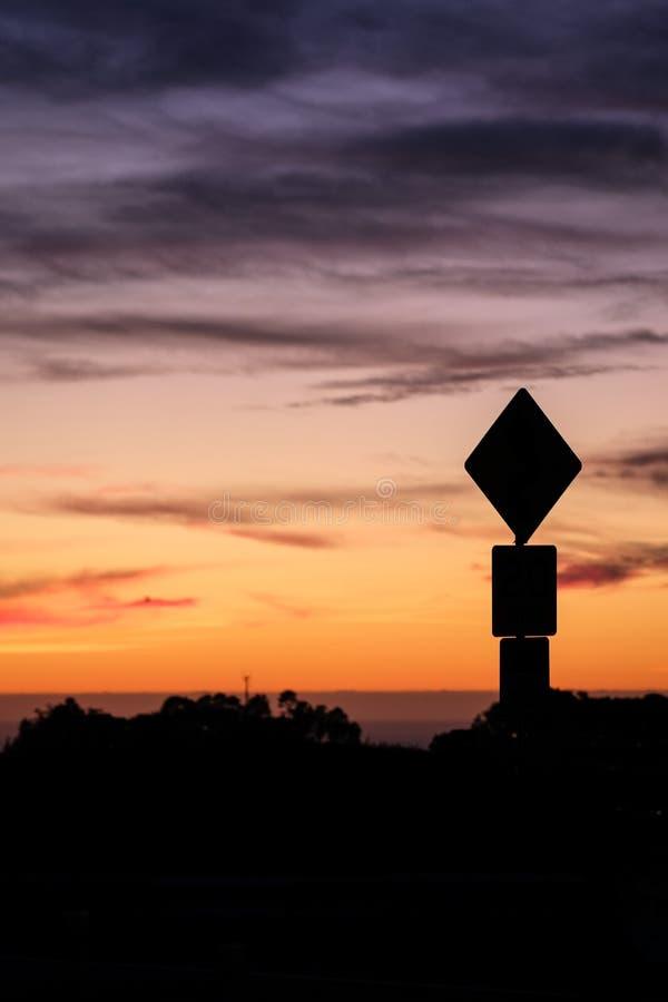 Siluetta del segnale stradale e tramonto variopinto immagini stock libere da diritti