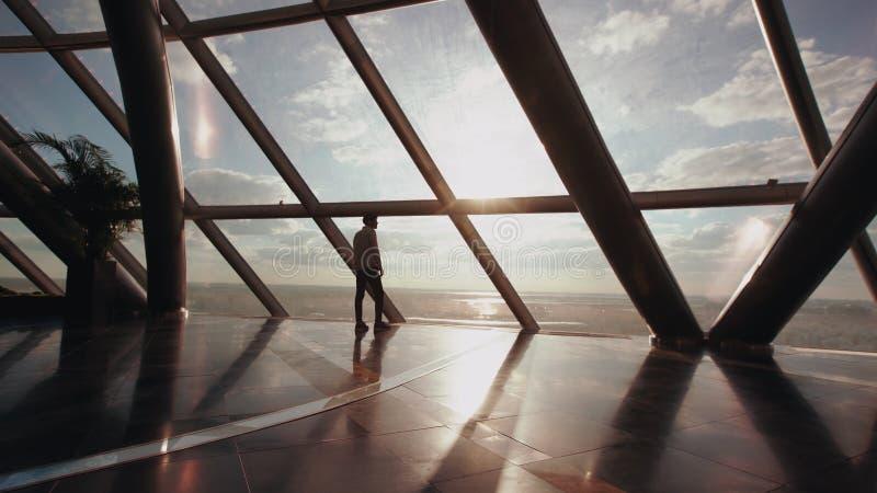 Siluetta del supporto dell'uomo d'affari vicino alla finestra nell'edificio per uffici moderno fotografia stock libera da diritti