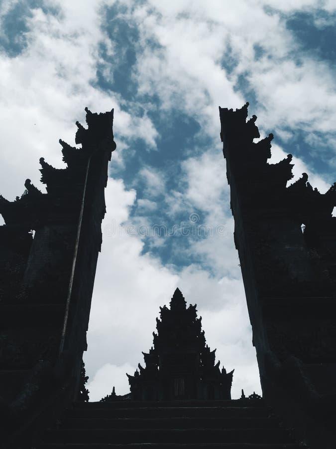 Siluetta del tempio di Bali al giorno soleggiato con il cielo nuvoloso a fondo, Indonesia fotografia stock