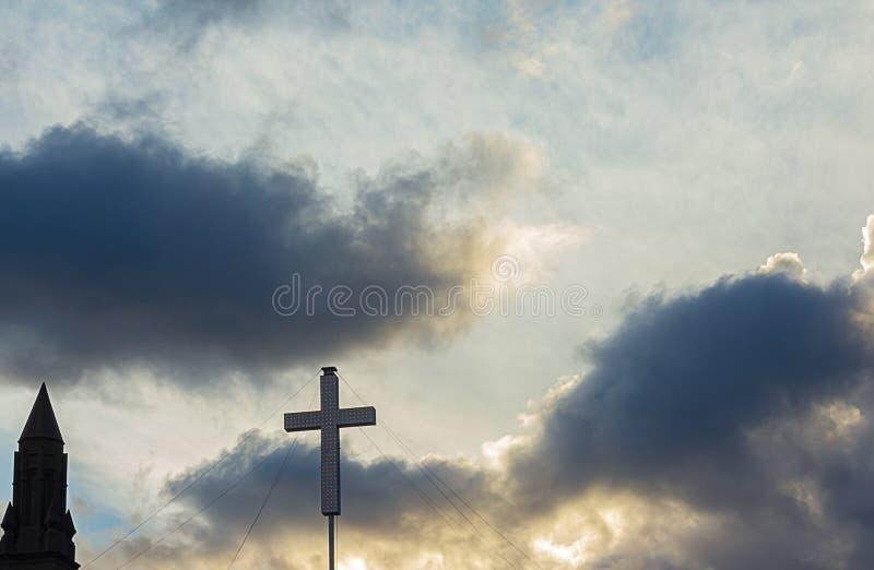 Siluetta del touret e dell'incrocio della costruzione contro il cielo nuvoloso di tramonto fotografia stock