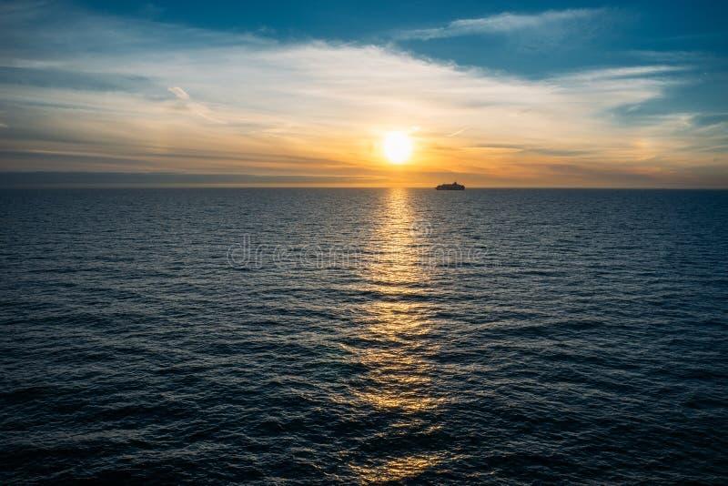 Siluetta del traghetto di crociera contro il tramonto immagini stock libere da diritti
