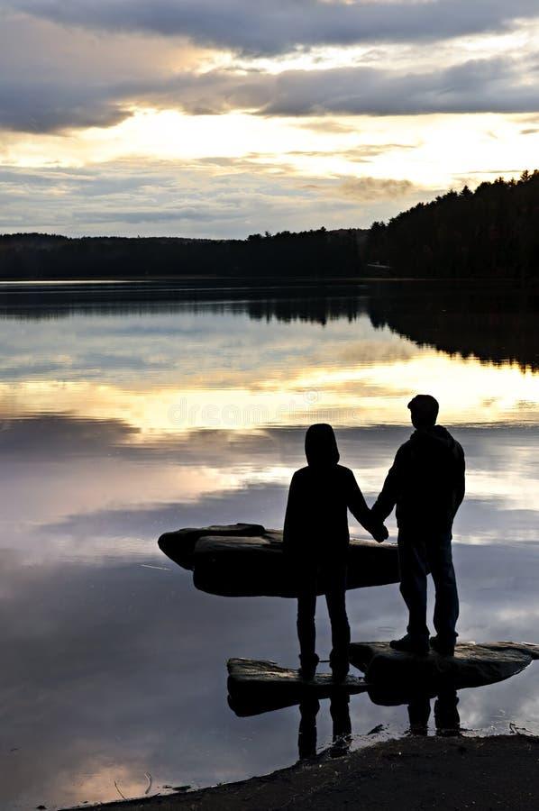 Siluetta del tramonto di sorveglianza della gente nel lago immagine stock libera da diritti