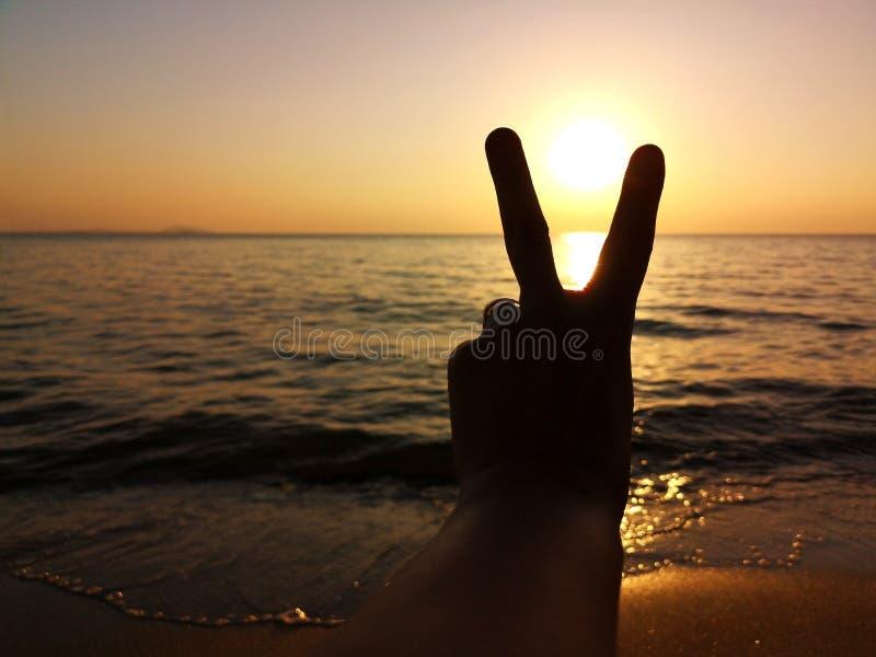 Siluetta del V-segno della tenuta della mano dell'uomo alla spiaggia mentre il tramonto Rinfreschi per il domani Scopo e concetto immagine stock
