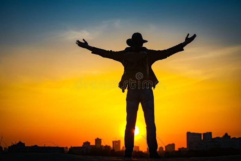 Siluetta del viaggiatore con uno zaino e un cappello da cowboy immagine stock libera da diritti