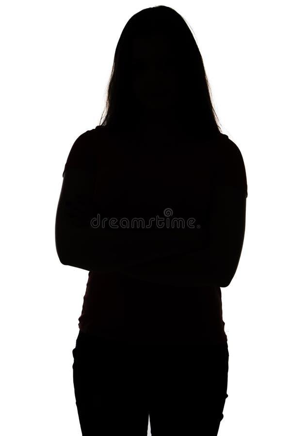Siluetta dell'adolescente con le armi attraversate fotografia stock libera da diritti