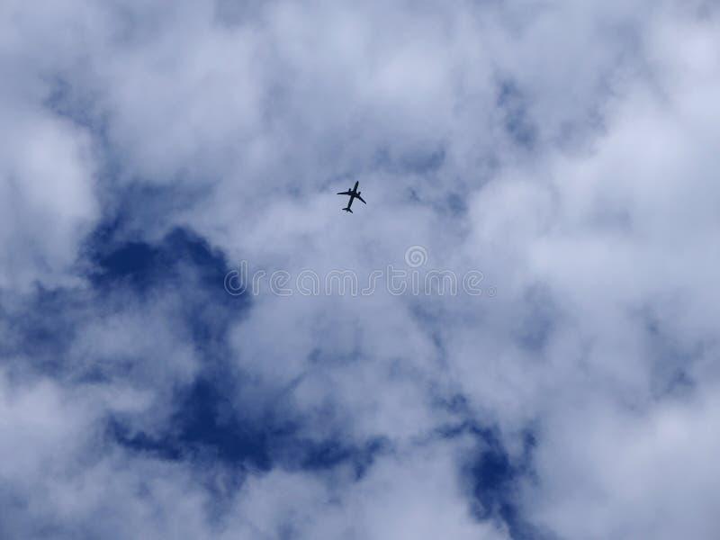 Siluetta dell'aeroplano su un fondo di cielo blu e delle nuvole bianche immagine stock libera da diritti