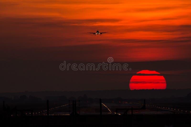 Siluetta dell'aeroplano sul tramonto, avvicinamento finale su Otopeni immagine stock