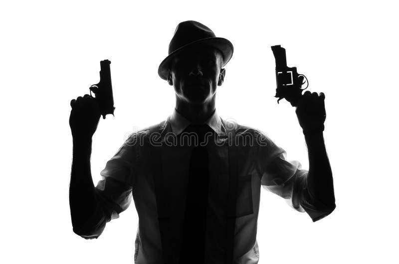 Siluetta dell'agente investigativo con due pistole fotografie stock libere da diritti