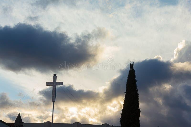 Siluetta dell'albero e dell'incrocio di cipresso contro il cielo nuvoloso di tramonto fotografie stock libere da diritti