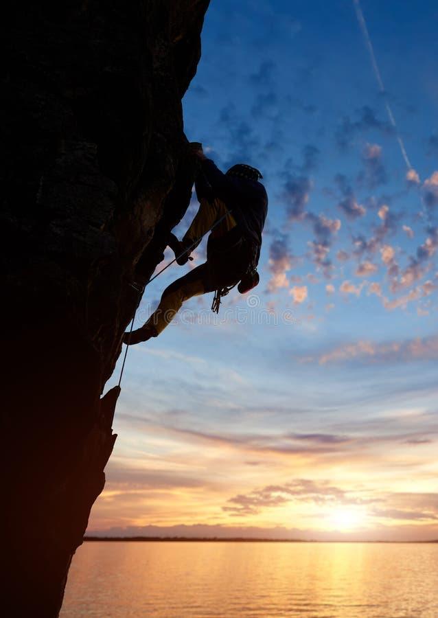 Siluetta dell'arrampicata dell'uomo alla sommit? della montagna Tramonto con il cielo nuvoloso blu sopra il fiume, spazio della c fotografie stock