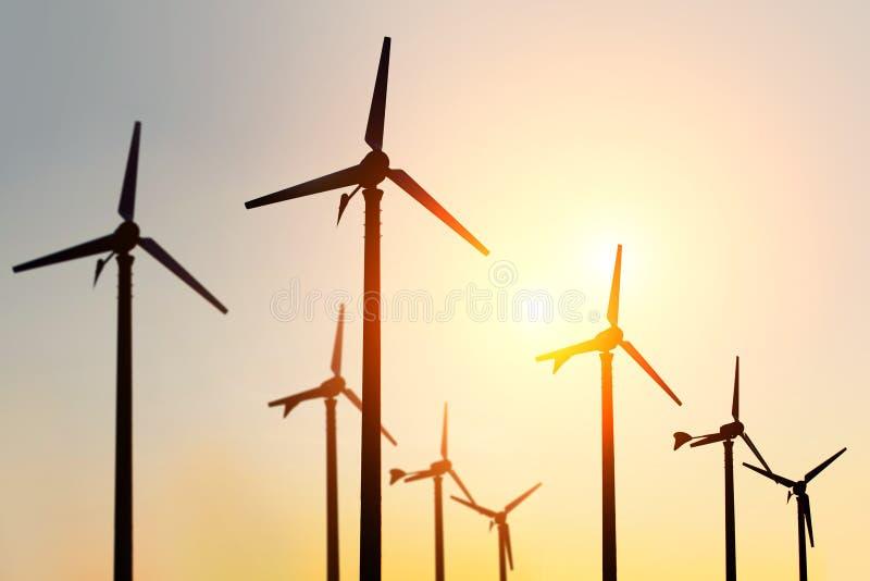 Siluetta dell'azienda agricola del generatore eolico sul tramonto fotografie stock libere da diritti