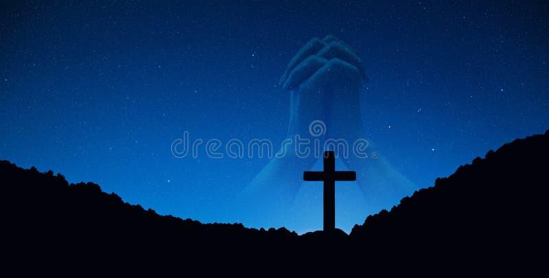 Siluetta dell'incrocio della croce sulla montagna alla notte con la mano che prega fondo fotografie stock