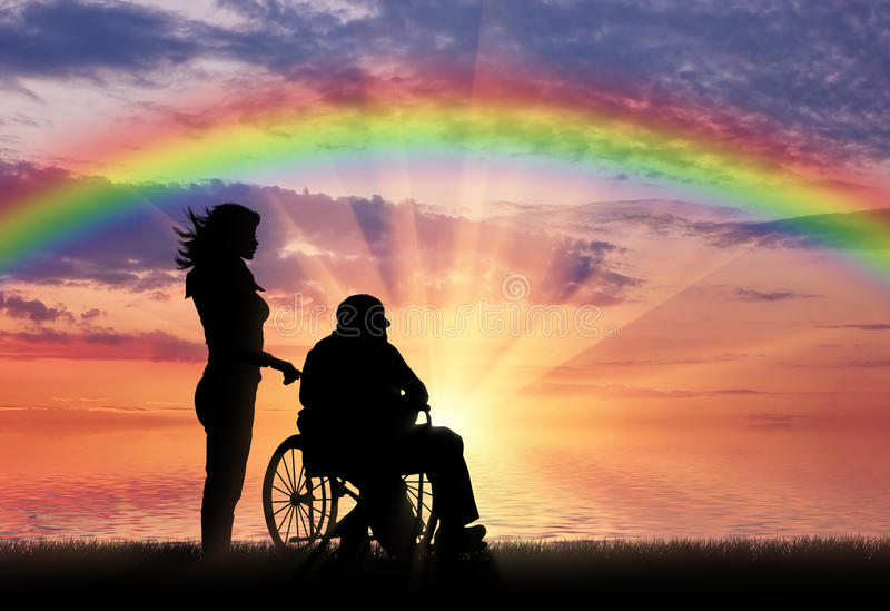 Siluetta dell'infermiere che si occupa di un disabile in una sedia a rotelle su un fondo dell'arcobaleno royalty illustrazione gratis