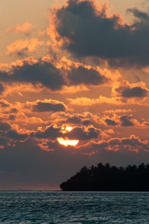 Siluetta dell'isola di palma nell'oceano al bello tramonto a immagine stock