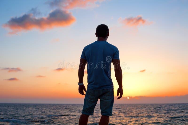 Siluetta dell'uomo al tramonto vicino al mare fotografia stock