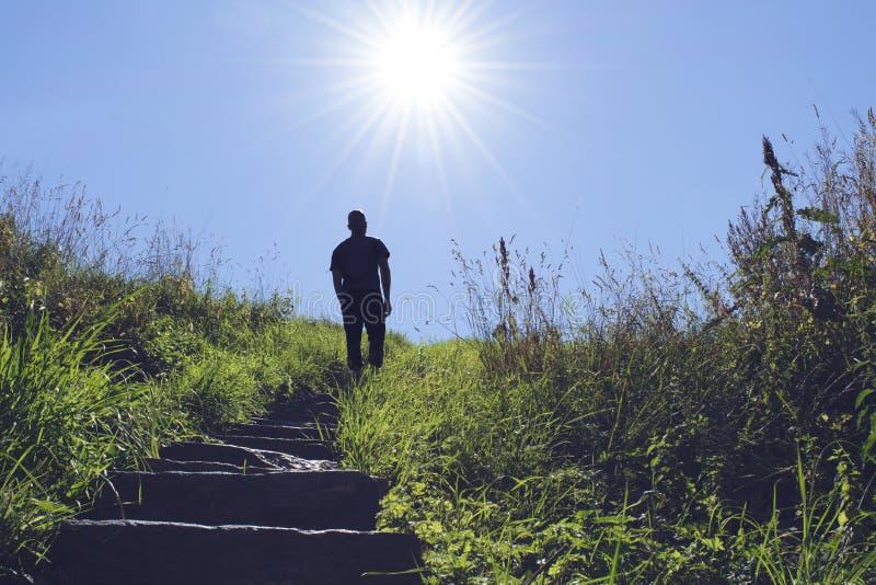 Siluetta dell'uomo che cammina su una scala verso il sole immagini stock libere da diritti