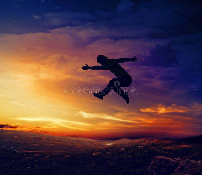 Siluetta dell'uomo che salta giù una scogliera fotografia stock