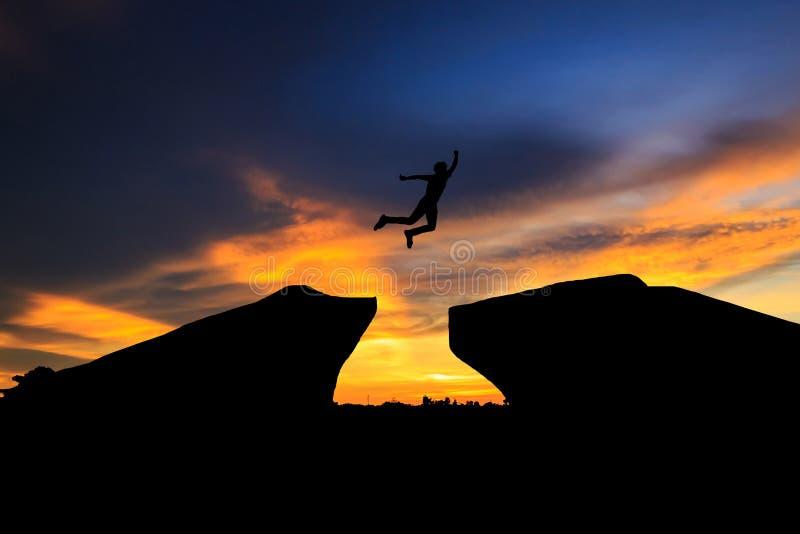 Siluetta dell'uomo che salta sopra la scogliera sul fondo di tramonto, fotografia stock libera da diritti