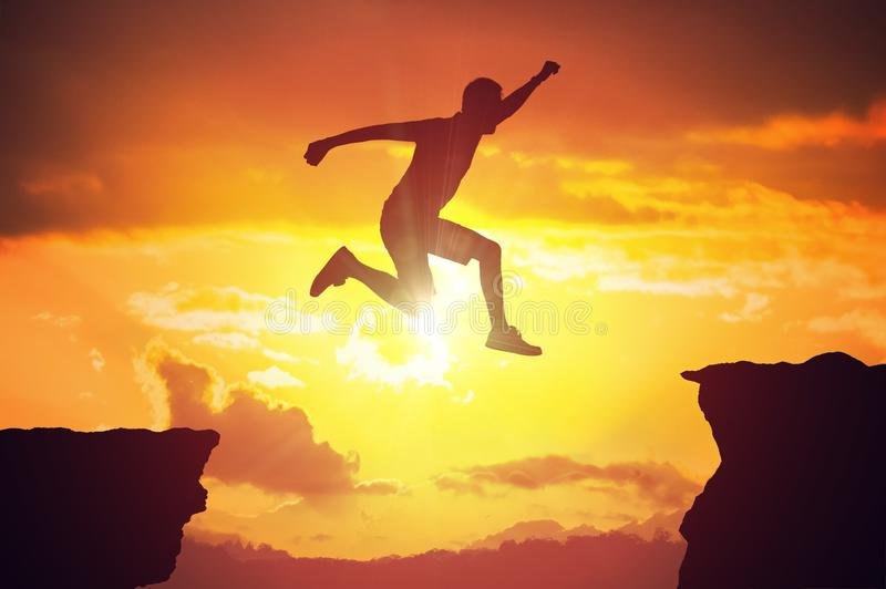 Siluetta dell'uomo che salta sopra una lacuna al tramonto fotografia stock