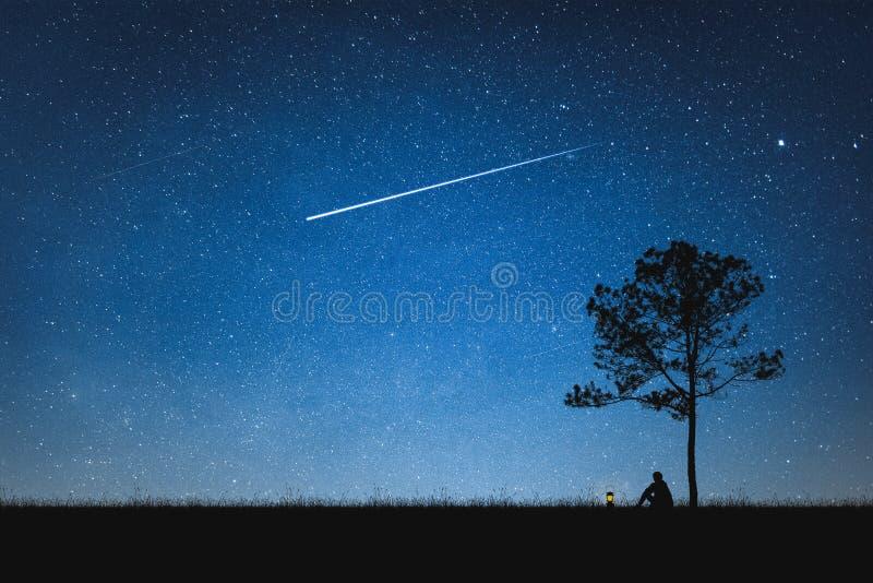 Siluetta dell'uomo che si siede sulla montagna e sul cielo notturno con la stella cadente concetto solo fotografie stock