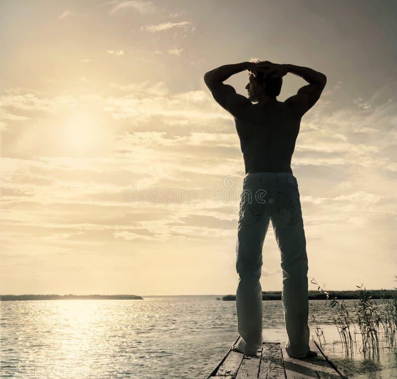Siluetta dell'uomo che sta sul piccolo molo di legno all'estate soleggiata immagine stock libera da diritti