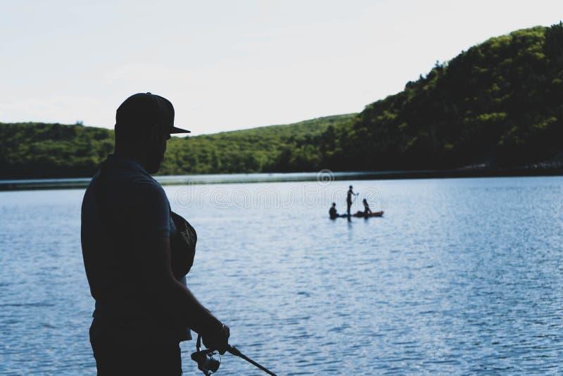 Siluetta dell'uomo con la canna da pesca sulla riva del lago e la gente che galleggia sulla barca davanti lui immagine stock libera da diritti