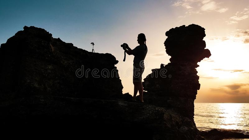 Siluetta dell'uomo con la macchina fotografica della foto in suoi mani e treppiede sulla pietra fotografia stock
