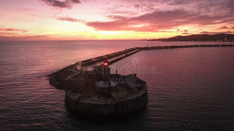 Siluetta dell'uomo Cowering di affari Faro di Laoghaire del Dun dublino l'irlanda fotografia stock