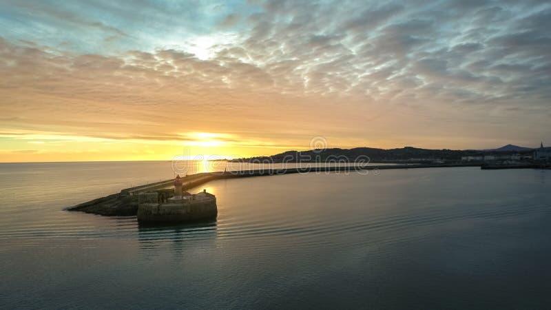 Siluetta dell'uomo Cowering di affari Faro di Laoghaire del Dun dublino l'irlanda immagine stock