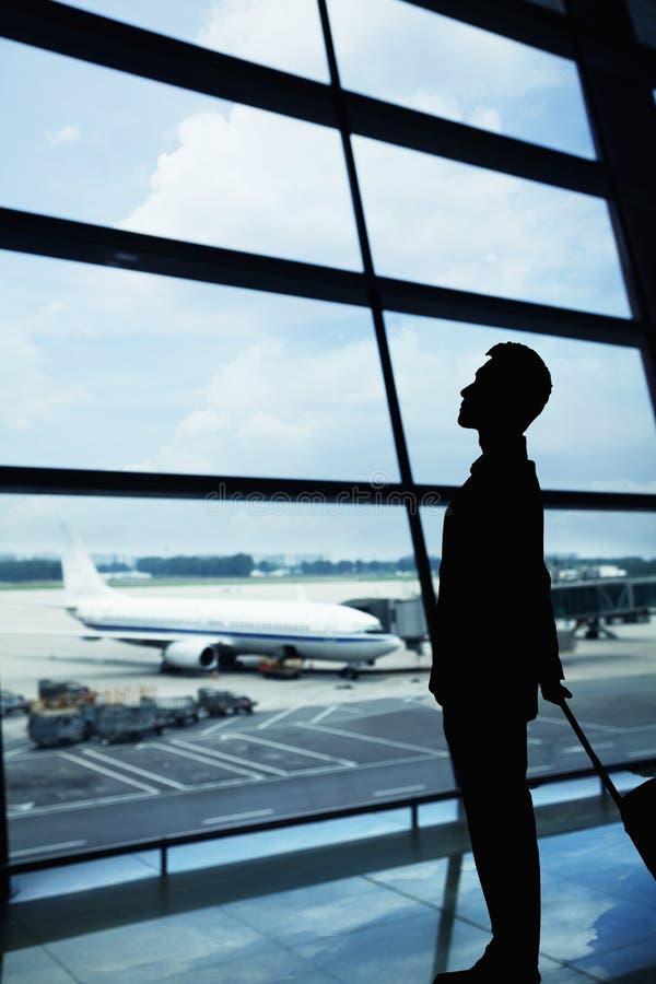 Siluetta dell'uomo d'affari che aspetta nell'aeroporto e che guarda fuori la finestra fotografia stock libera da diritti