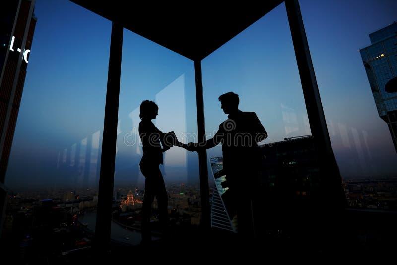 Siluetta dell'uomo d'affari che stringe le mani in onore della transazione con il suo nuovo partner della donna fotografia stock libera da diritti
