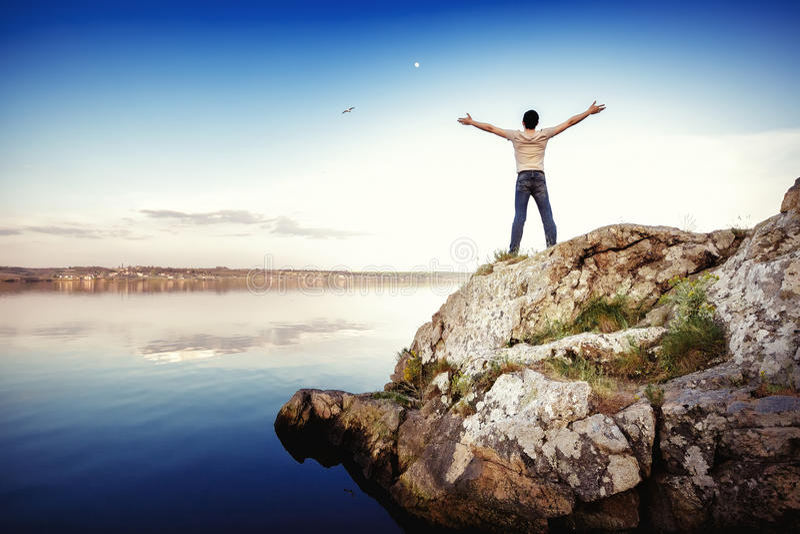 Siluetta dell'uomo felice che sta sulla roccia e delle armi stese contro il cielo Libertà fotografia stock