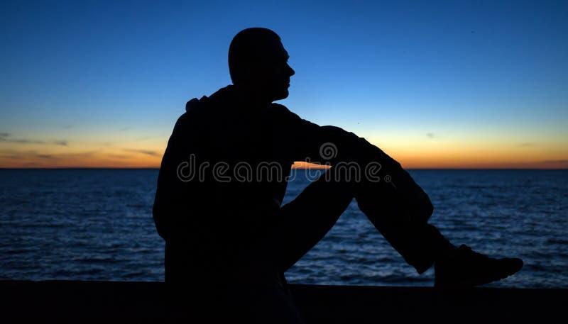 Siluetta dell'uomo premuroso calmo che guarda il tramonto fotografie stock