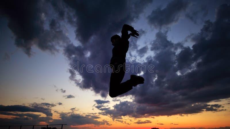 Siluetta dell'uomo sul tetto Nubi e tramonto immagine stock