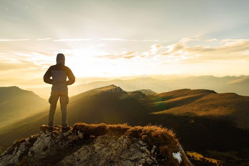 Siluetta dell'uomo sulla cima il picco della montagna su alba fotografia stock libera da diritti