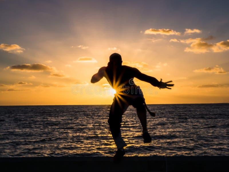 Siluetta dell'uomo sulla spiaggia al tramonto immagine stock