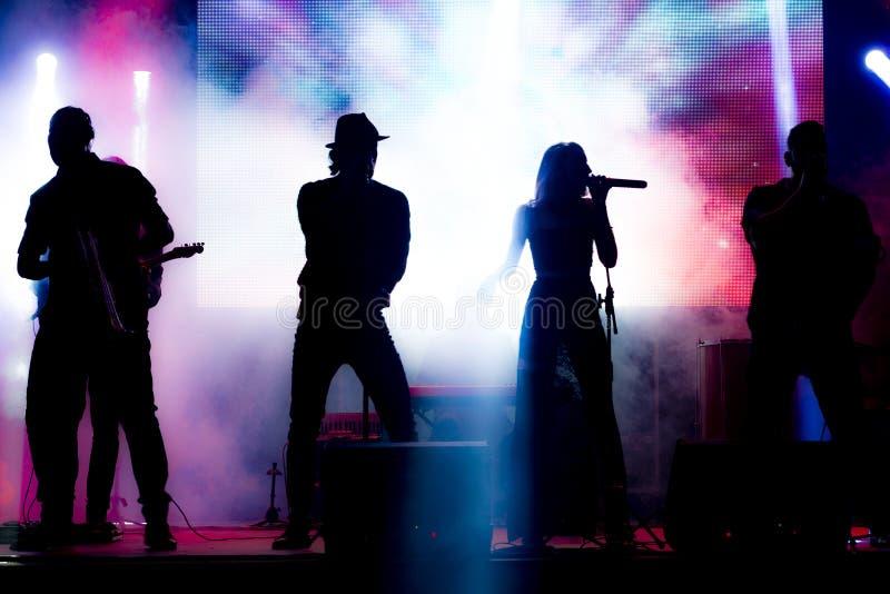 Siluetta della banda nella presentazione musicale nell'evento fotografie stock
