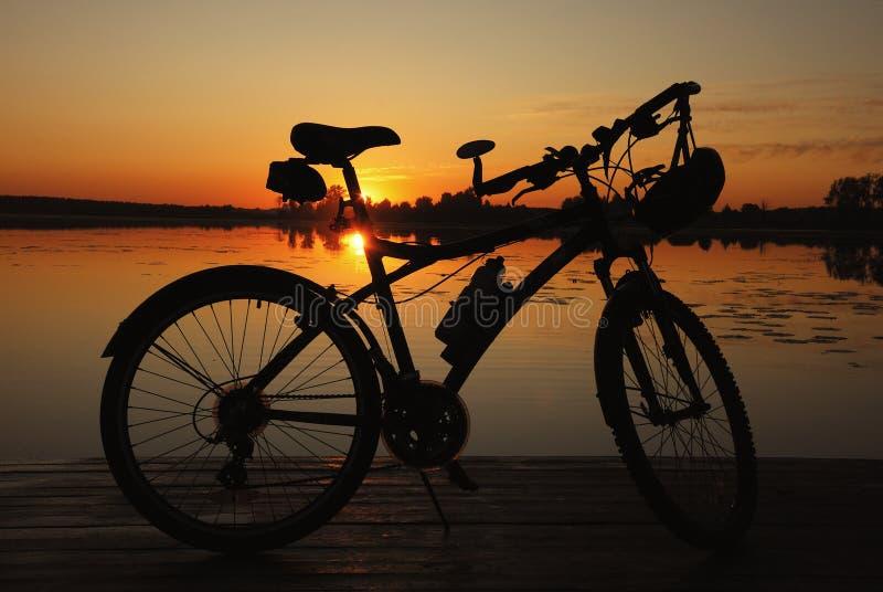 Siluetta della bici sul tramonto fotografia stock libera da diritti