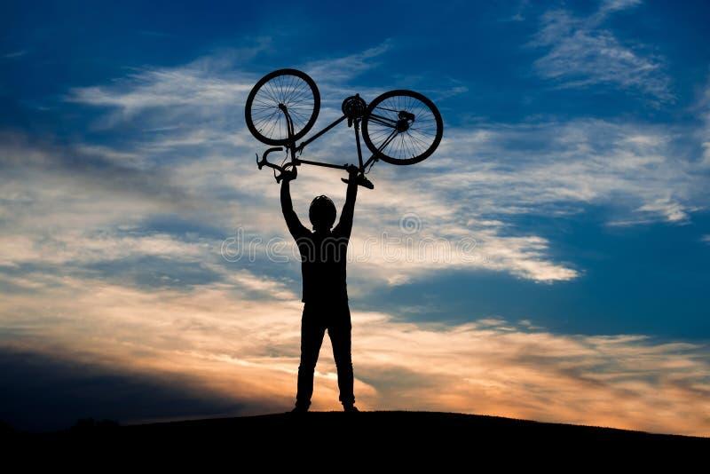 Siluetta della bicicletta di sollevamento del ciclista al tramonto immagine stock libera da diritti