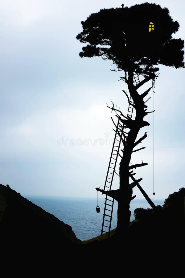 Siluetta della casa sull'albero fotografia stock