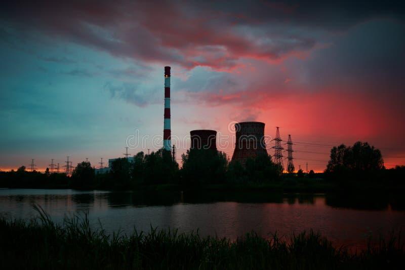 Siluetta della centrale elettrica elettrica della turbina a gas contro il cielo di tramonto fotografia stock