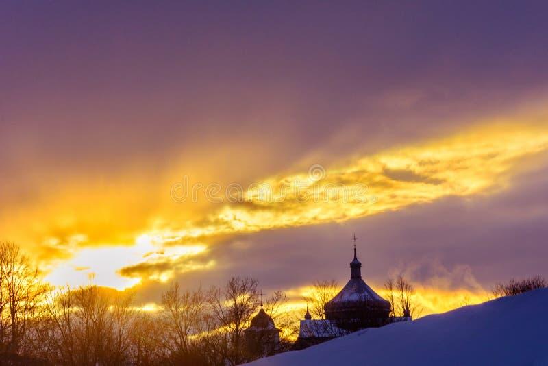 Siluetta della chiesa nel villaggio ucraino al tramonto nell'inverno fotografie stock