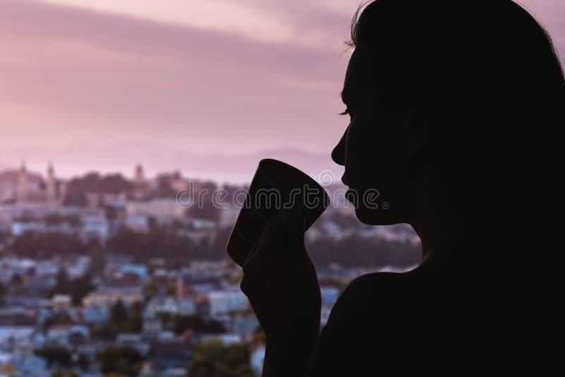 Siluetta della donna con la tazza di tè sui precedenti della città di Chicago fotografia stock libera da diritti